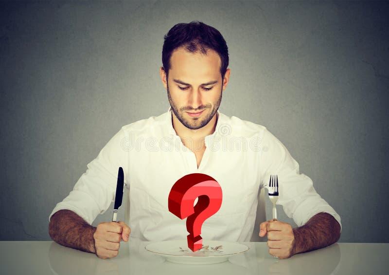 Man med gaffel- och knivsammanträde på tabellen som ser plattan med stor röd fråga arkivbilder