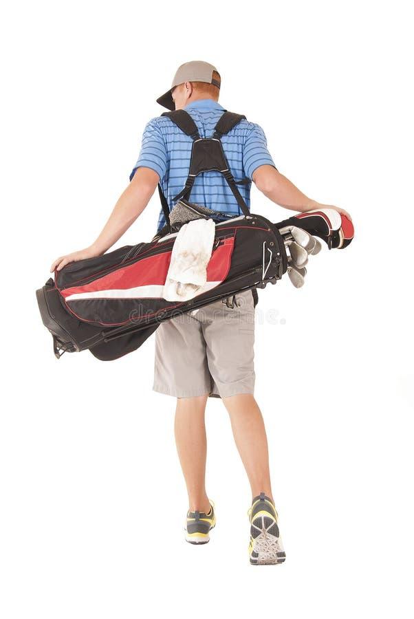 Man med golfpåsen som går i väg från kameran arkivbilder