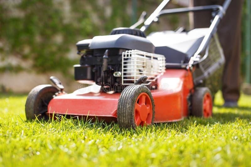 Man med gräsklipparen royaltyfri foto