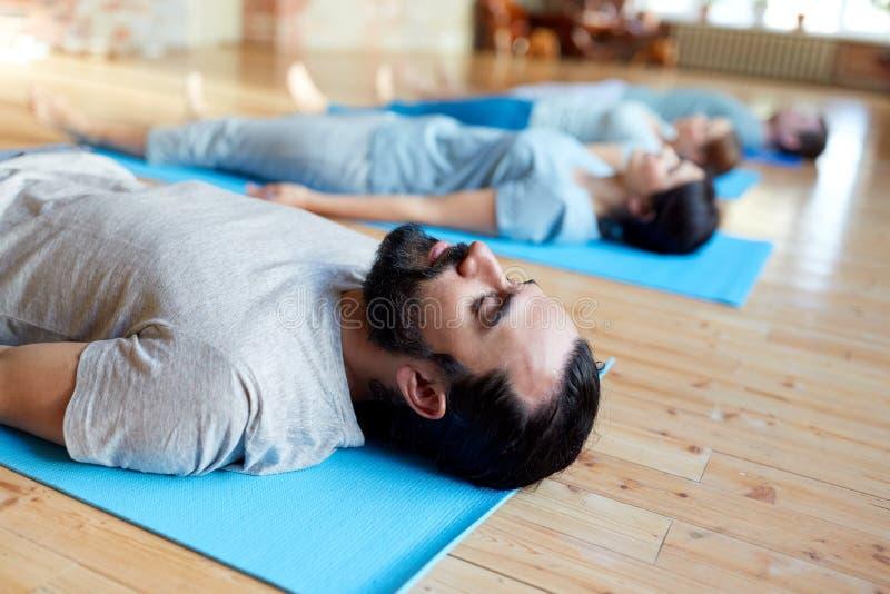 Man med grupp människor som gör yoga på studion royaltyfri fotografi