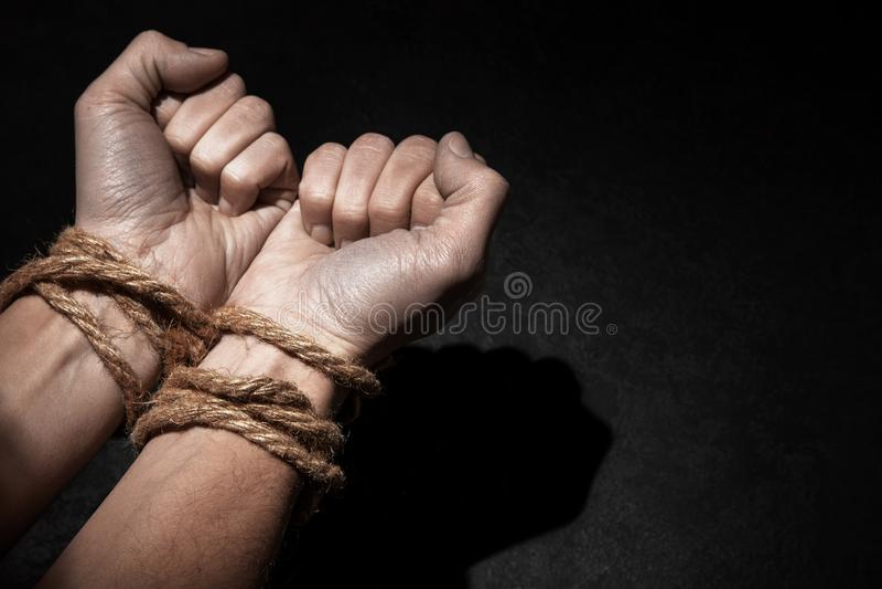 Man med händer som binds med repet på svart bakgrund Begreppet av slaveri eller fången Kopiera utrymme för text royaltyfria bilder