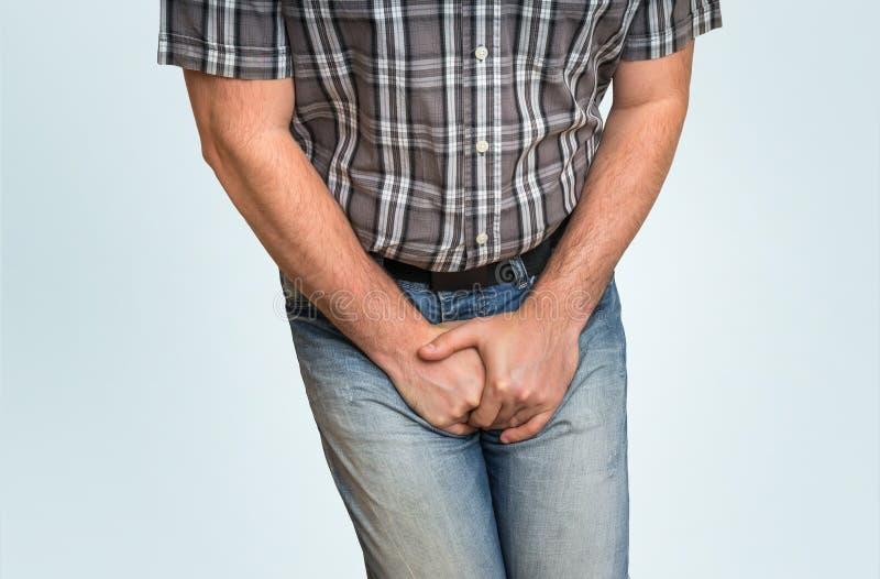 Man med händer som rymmer hans klyka, honom önskar att kissa arkivbilder