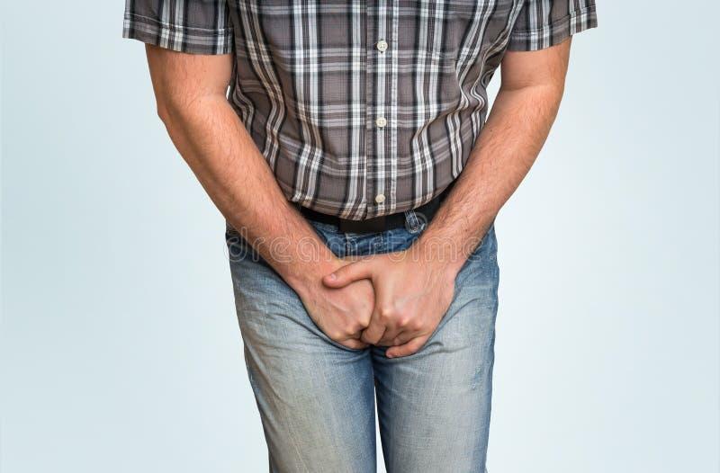 Man med händer som rymmer hans klyka, honom önskar att kissa arkivfoton