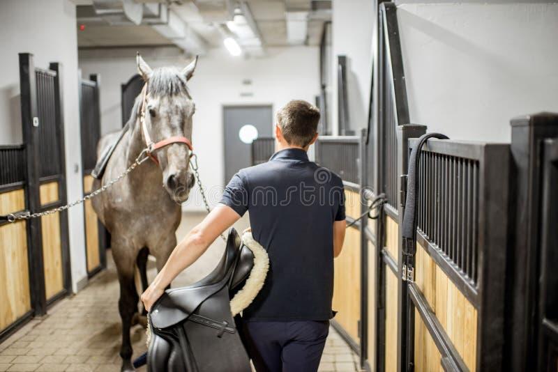 Man med hästen i stallet royaltyfri bild