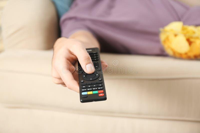Man med hållande ögonen på TV för fjärrkontroll på soffan arkivbild