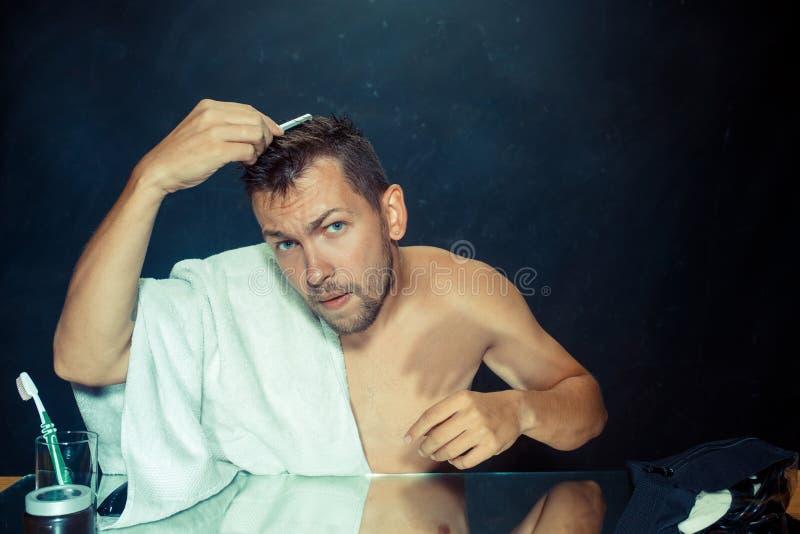 Man med hårkammen som angås om hårförlust fotografering för bildbyråer