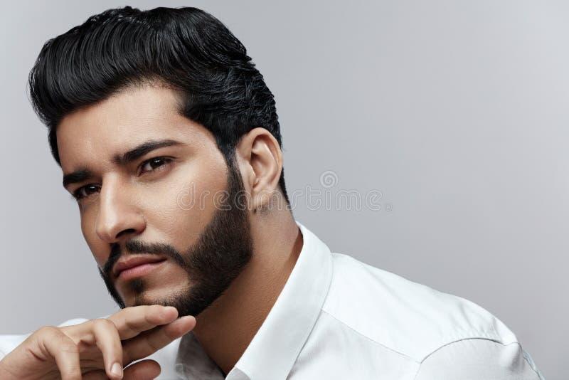 _ Man med hårstil och skäggståenden stilig manlig arkivbild