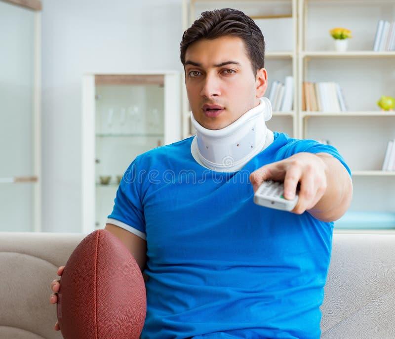 Man med halsskada som hemma h?ller ?gonen p? amerikansk fotboll arkivfoto