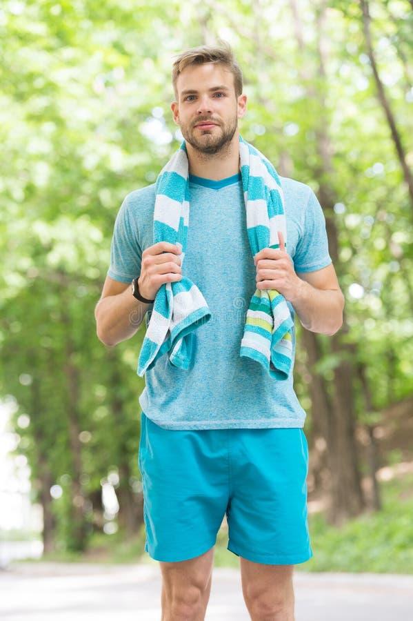 Man med handduken på naturligt landskap Idrottsman, precis når utbildning svettigt trött Sommarstrandtid och semester arkivbild