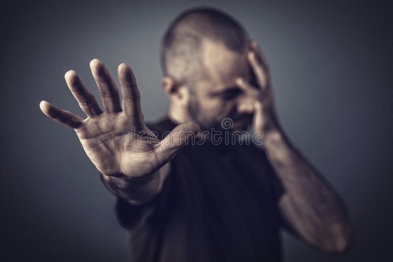 Man med handen på hans framsida och en annan hand som framåtriktat lutar för att skydda sig fotografering för bildbyråer