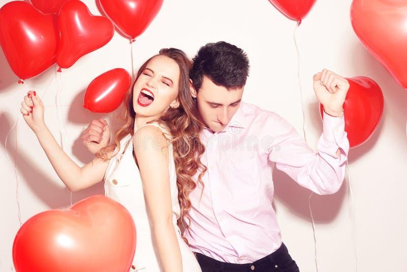Man med hans älskvärda älsklingflickadans och att ha gyckel på väns valentindagen Valentine Couple Koppla ihop jätteglat, partiti arkivbilder