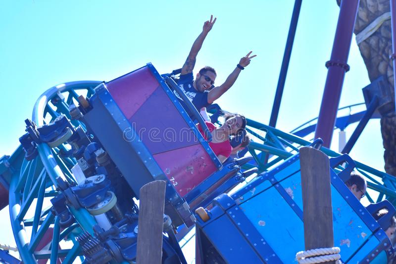 Man med hans händer upp och kvinnan som tycker om rollercoasterritt på Bush trädgårdar Tampa Bay fotografering för bildbyråer