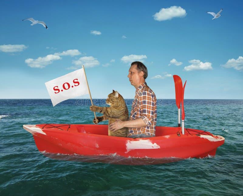 Man med hans katt i en röd kajak royaltyfria bilder