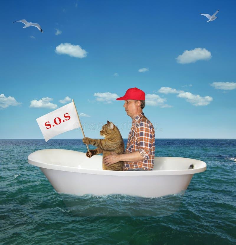 Man med hans kattdriva på havet fotografering för bildbyråer