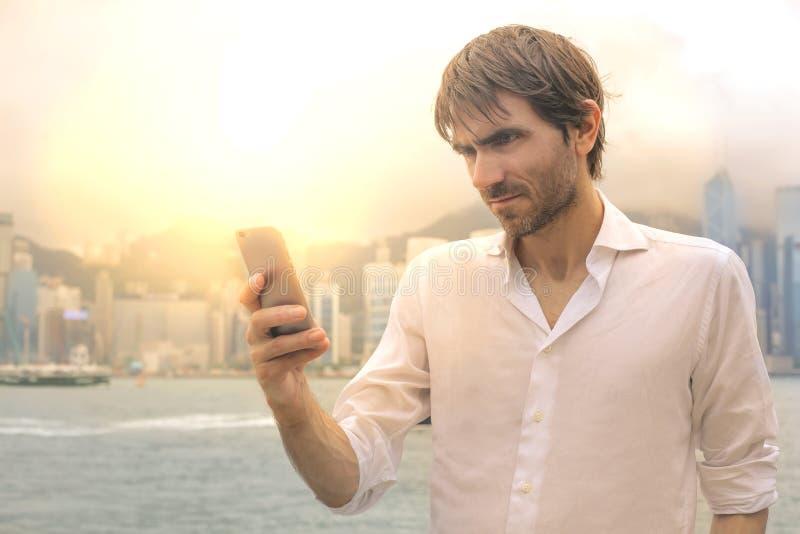Man med hans mobiltelefon royaltyfri foto
