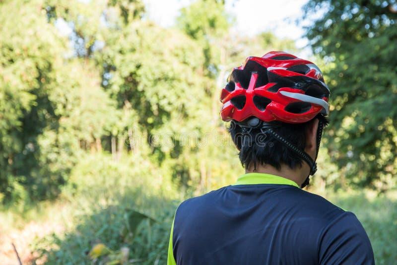 Man med hjälmhandsken för säkerhet som rider en cykel på bygdvägen längs en skog, ridning för argt land som cyklar aktivitet och royaltyfri bild