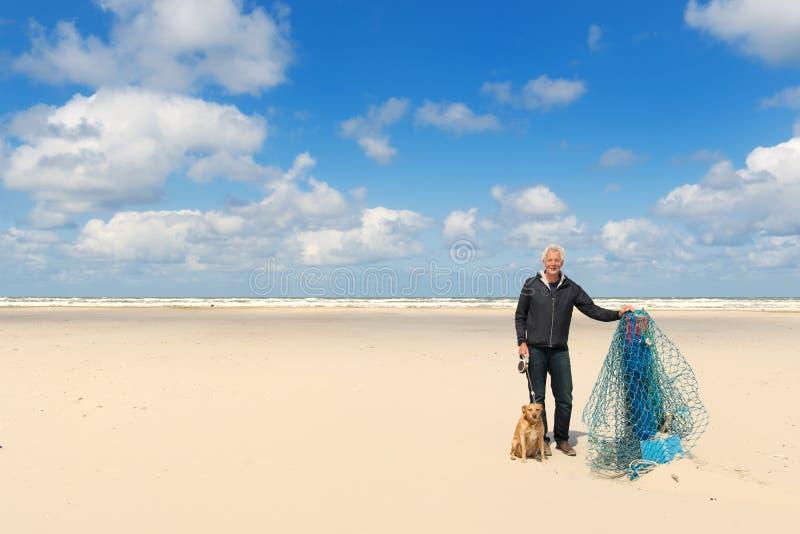Man med hunden på stranden royaltyfria foton