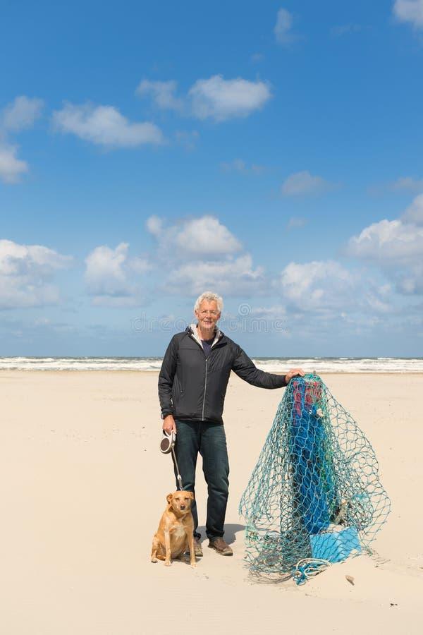 Man med hunden på stranden royaltyfri bild