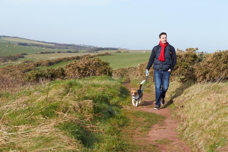 Man med hunden som promenerar den kust- banan arkivfoto