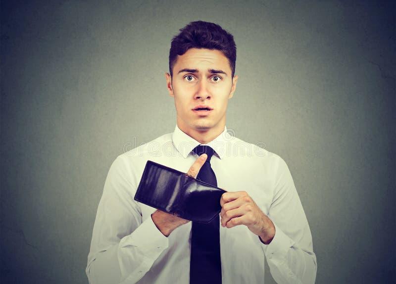 Man med inga pengar Ung affärsman som rymmer den tomma plånboken arkivfoto