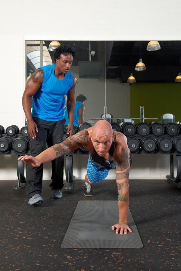 Man med instruktören i idrottshall royaltyfri foto
