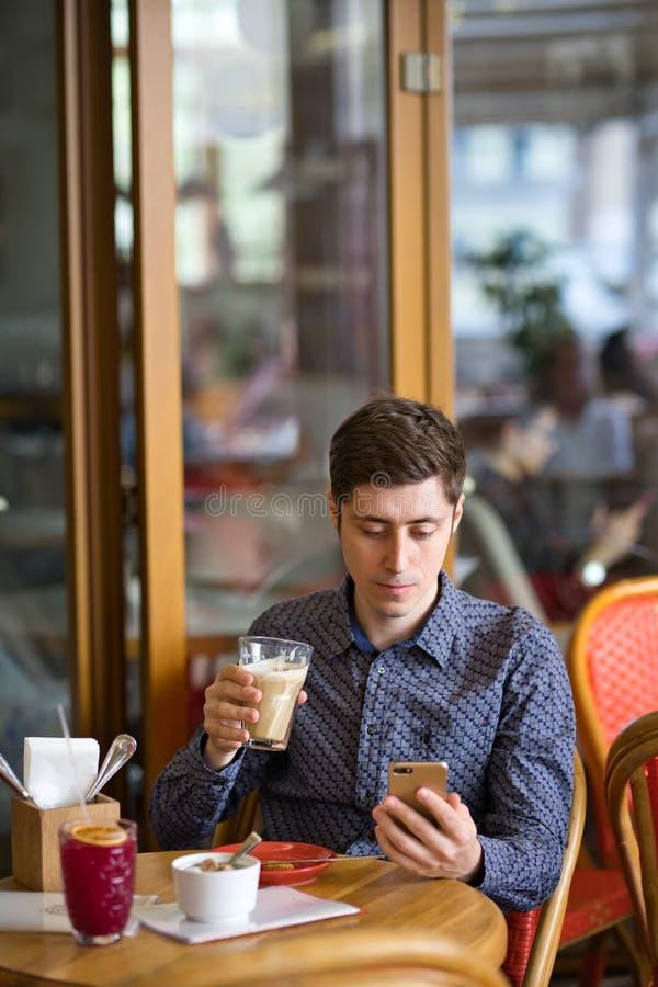 Man med kaffe och smartphonen arkivfoton