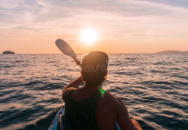 _ Man med kajakskoveln på solnedgånghavet som ror till solen arkivbild