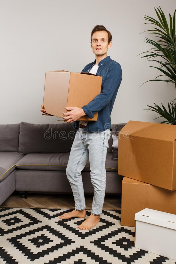 Man med kartongen i händer på bakgrund av den gråa soffan, inomhus växter royaltyfri foto