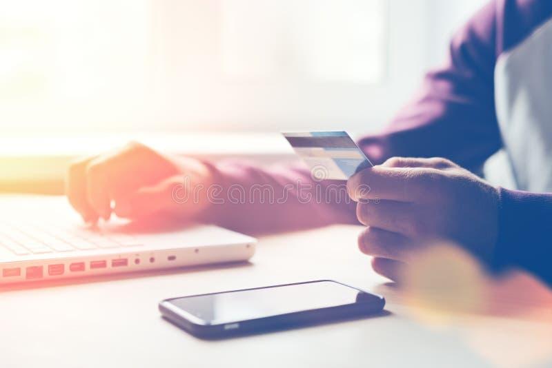 Man med kontokortet och bärbar dator som gör online-shopping royaltyfri foto
