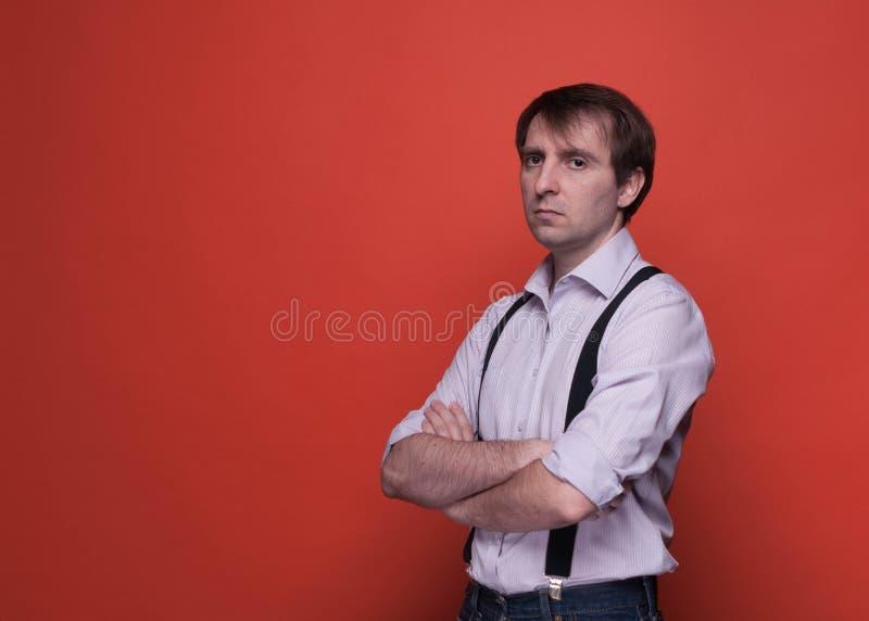Man med korsade armar i rosa skjorta och svarta suspenderen som ser kameran på orange bakgrund royaltyfri foto