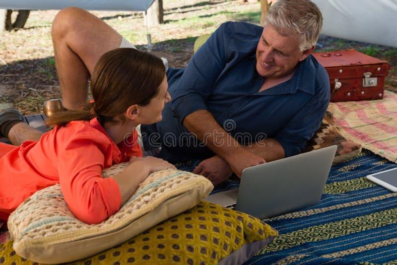 Man med kvinnan som använder bärbara datorn i tält royaltyfri foto