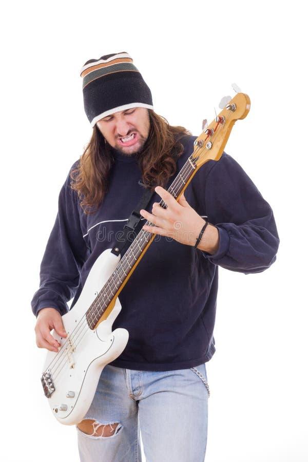 Man med långt hår som spelar en gitarr royaltyfria foton