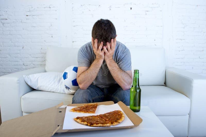Man med leken för fotboll för för bollpizza och ölflaska den hållande ögonen på på tvbeläggningögon som är ledsna och som är besv arkivfoton