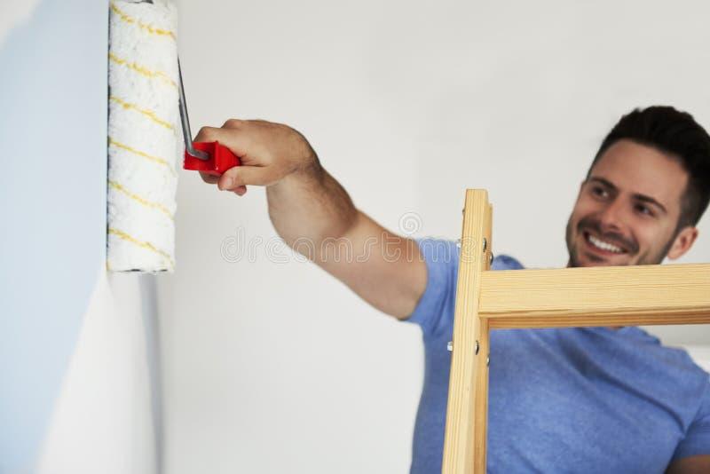 Man med målarfärgrullen som målar väggar i hans lägenhet royaltyfri bild