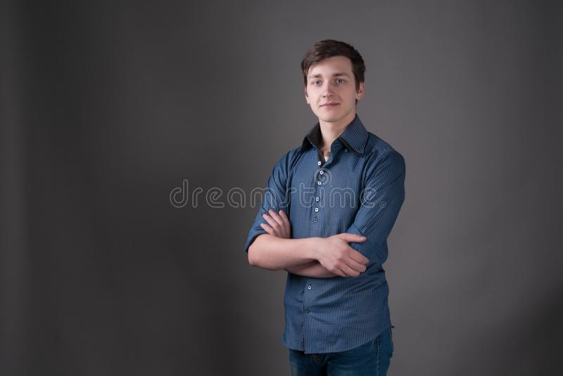 man med mörkt hår i blått skjortaanseende med korsade armar royaltyfri foto