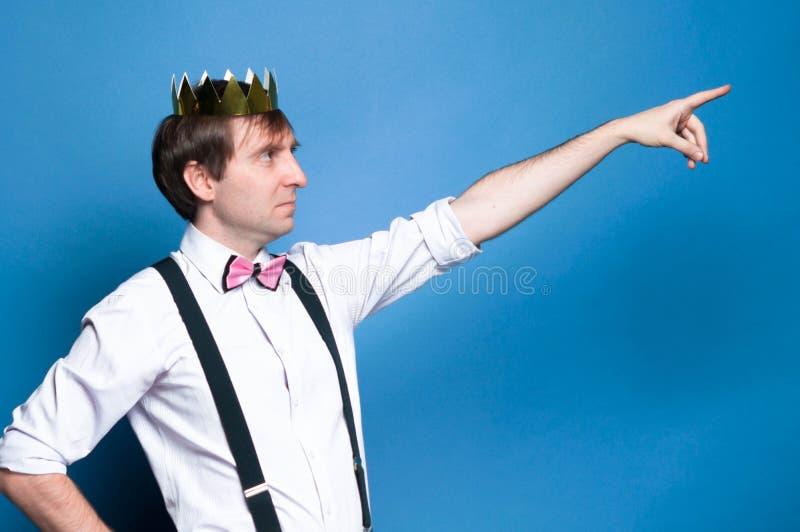 Man med mörkt hår i rosa skjorta, fluga, suspender och guld- skinande hemlagad krona som pekar med fingret till bort royaltyfria bilder