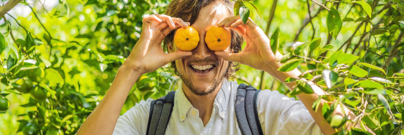 Man med manlarinas på ett tangerinkoloniBANER, LÅNGT FORMAT royaltyfri bild