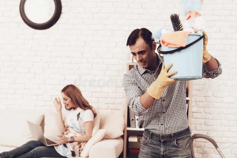 Man med mer ren tillbehör och kvinna i soffa arkivfoto
