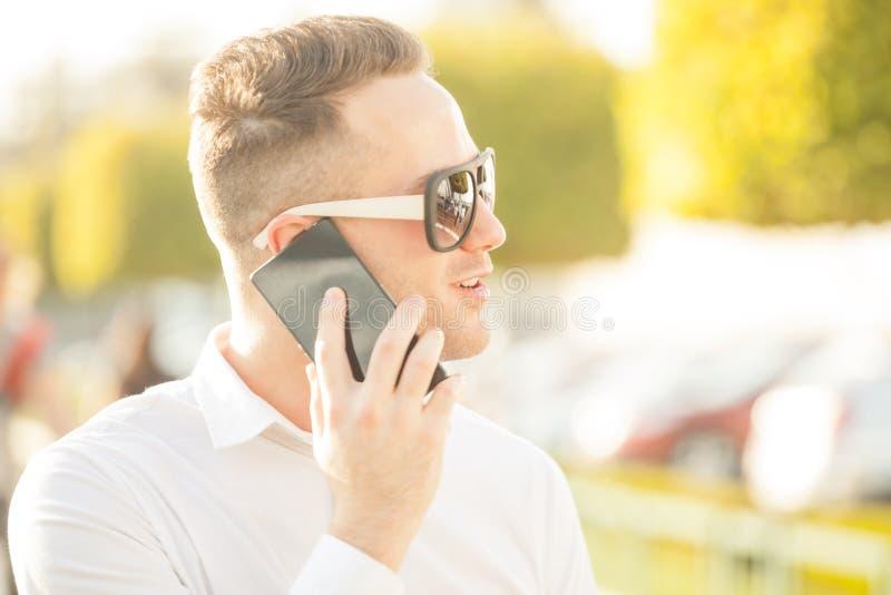 Man med mobiltelefonen i händer arkivbilder