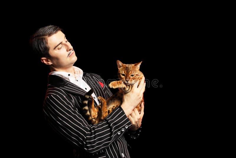 Man med mustaschen i svart dräkt med en katt fotografering för bildbyråer