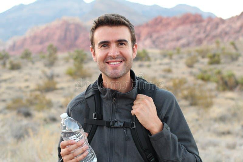 Man med passformkroppdricksvatten som vilar efter rinnande genomkörare Törstig man som dricker den uppfriskande drinken efter uto arkivbild