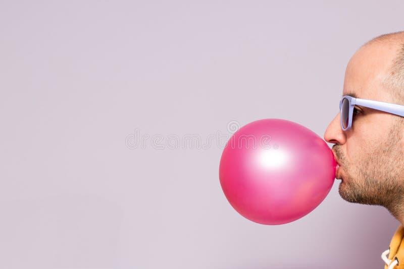 Man med purpurfärgad solglasögon som blåser rosa tuggummi som förläggas på rätsidan av bilden royaltyfria foton