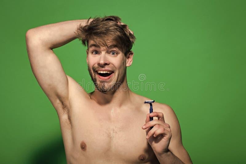 Man med rakknivleende med den halva rakade och skäggiga framsidan fotografering för bildbyråer
