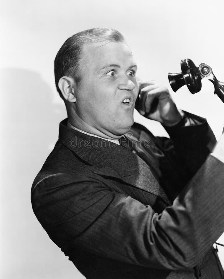 Man med roligt uttryck genom att använda telefonen (alla visade personer inte är längre uppehälle, och inget gods finns Leverantö arkivfoton