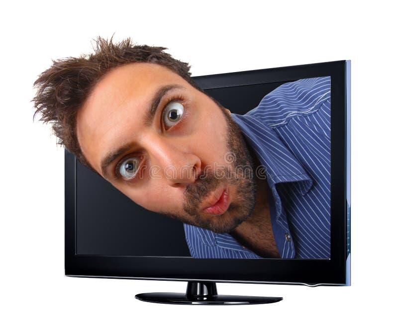 Man med roligt uttryck som hoppar ut ur TV:N, effekt 3d royaltyfria foton