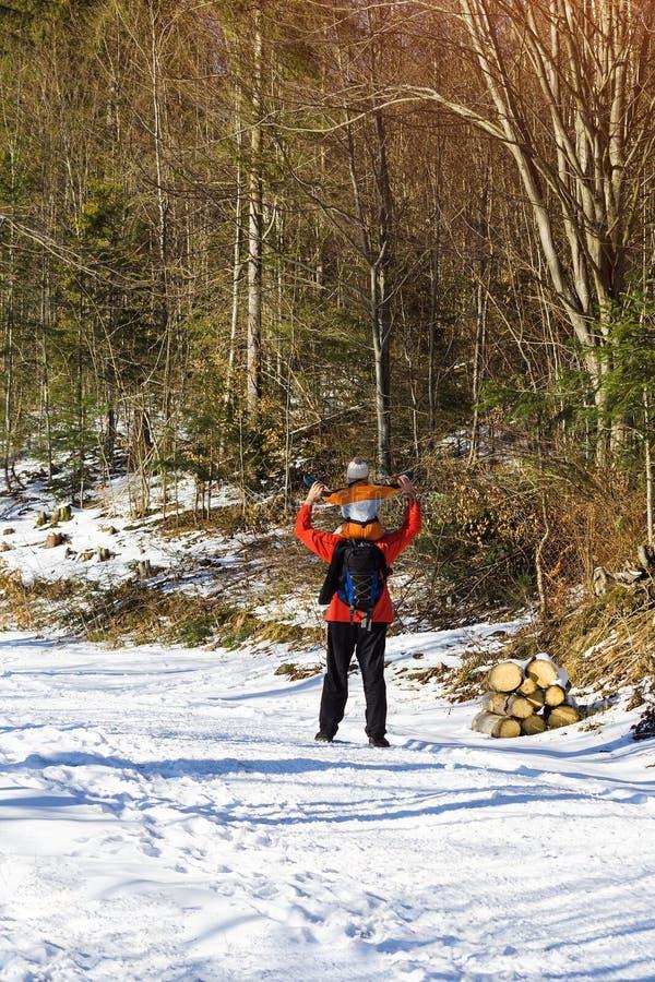 Man med ryggsäcken och sonen på skuldraställningar med lyftta armar mot bakgrunden av barrträd i skogvintern royaltyfria foton