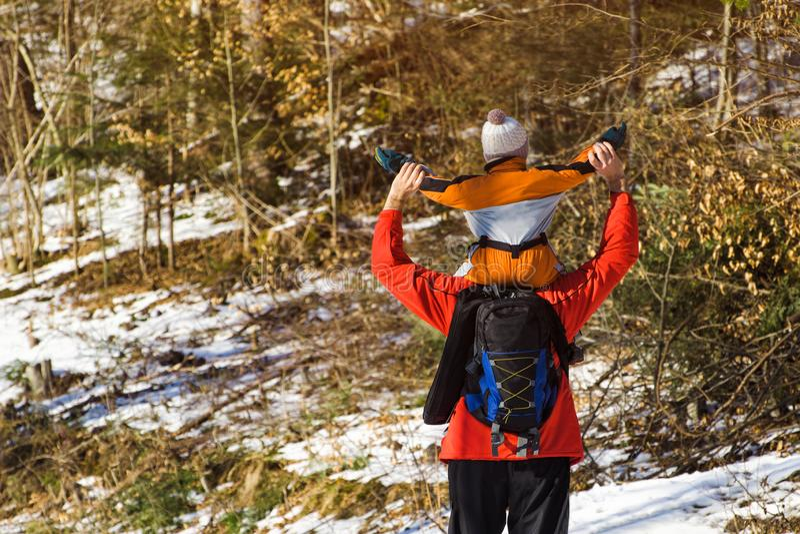 Man med ryggsäcken och sonen på skuldraställningar med lyftta armar mot bakgrunden av barrträd i skogvintern arkivfoto