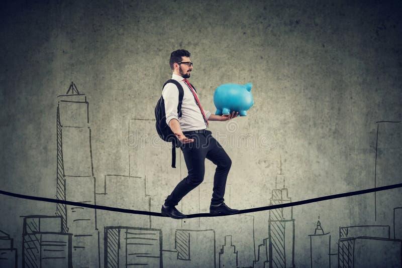 Man med ryggsäcken och spargrisen som går att balansera på ett rep ovanför en stadshorisont royaltyfria bilder