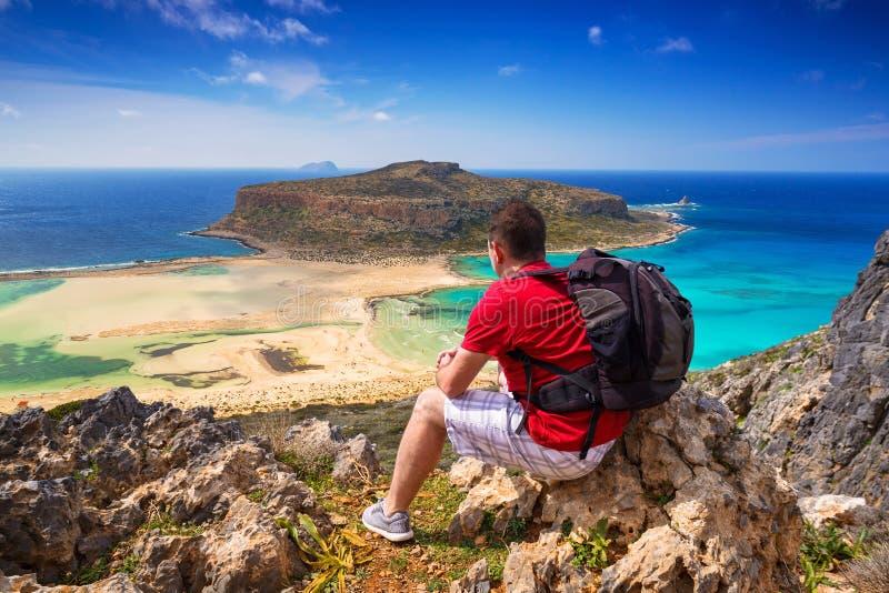 Man med ryggsäcken som håller ögonen på den härliga Balos stranden på Kreta, Greec royaltyfria foton