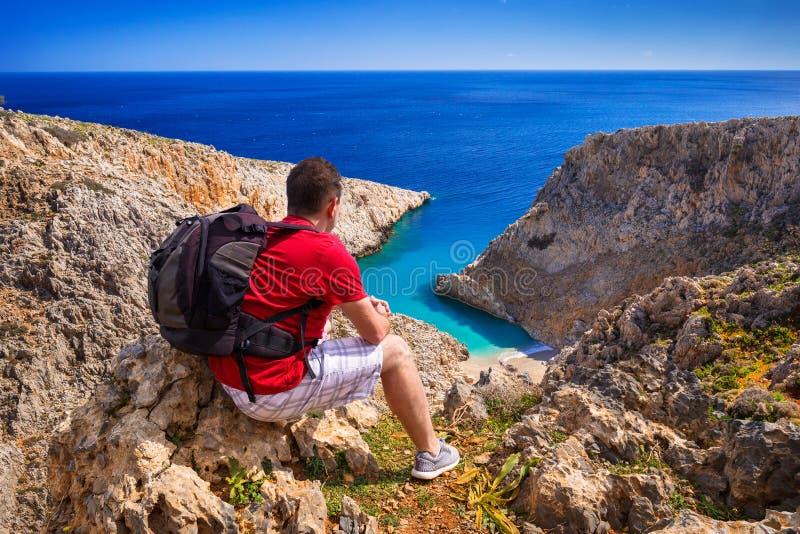 Man med ryggsäcken som håller ögonen på den härliga stranden på Kreta arkivbild